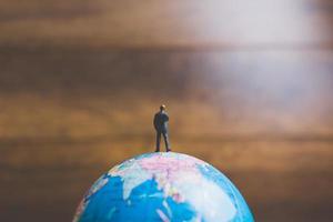 homme d'affaires miniature debout sur une carte du monde globe avec un fond marron