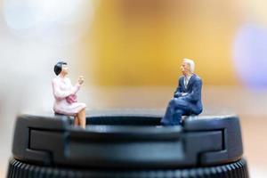 Hommes d & # 39; affaires miniatures assis avec un fond coloré bokeh photo