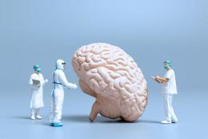 Médecins miniatures vérifiant et analysant un cerveau pour les signes de la maladie d'Alzheimer et de la démence, la science et le concept de médecine