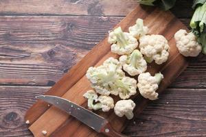 couteau et chou-fleur sur planche à découper photo