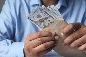 la main de la personne mettant de l'argent dans une enveloppe photo