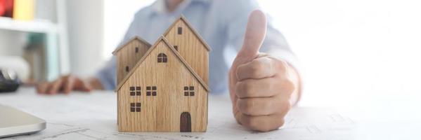 Thumbs up part de l'agent bancaire confirme le succès de l'immobilier, le concept photo