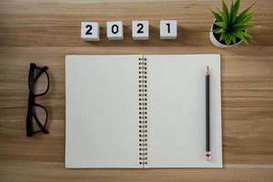 Cahier de papier vide avec le numéro de l'année 2021 pour la planification sur fond de table en bois