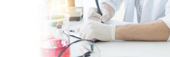 chimiste ou médecin recherchant et testant des médicaments et trouvant des informations sur un ordinateur portable photo