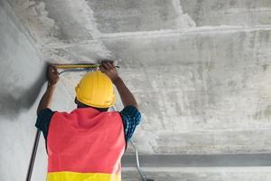 Inspecteur vérifiant et mesurer un ruban à mesurer dans le bâtiment photo