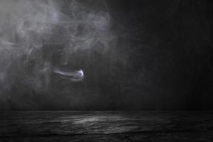 Studio de sol en ciment et en pierre et fond intérieur noir avec brouillard photo