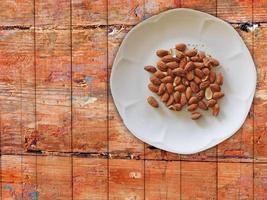 Amandes sur plaque blanche sur fond de table en bois photo