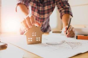 Ingénieur architecte travaillant sur des plans et touchant le modèle de la maison photo