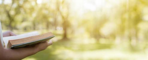 concept de lecture et de connaissances, main tenant un livre sur fond de bannière de parc vert doux photo
