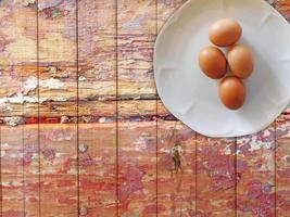 Oeufs bruns sur une plaque blanche sur un fond de table en bois photo