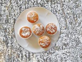 Muffins sur une plaque blanche sur un fond de mur de pierre ou de roche photo