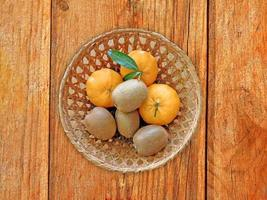 Les kiwis et les oranges dans un panier en osier sur un fond de table en bois photo