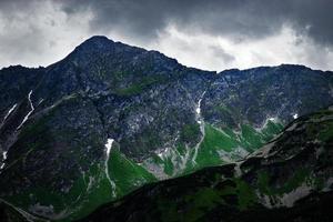 ciel sombre sur un pic rocheux dans les montagnes photo