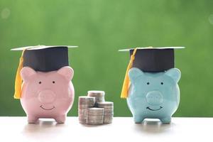 Chapeaux de graduation sur les tirelires et une pile de pièces sur un fond vert naturel, économiser de l'argent pour le concept de l'éducation photo