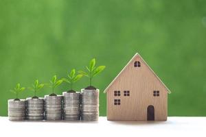 Les plantes poussant sur une pile de pièces et une maison modèle sur un fond vert naturel, les taux d'intérêt et le concept bancaire photo