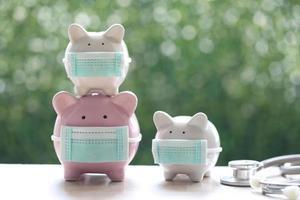 Tirelires portant des masques médicaux de protection sur un fond vert naturel, économisez de l'argent pour l'assurance médicale et le concept de soins de santé