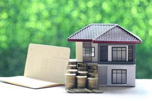 Maison modèle et une pile de pièces avec un livre de compte bancaire sur un fond vert naturel, investissement des entreprises et concept immobilier
