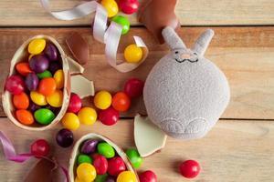 lapin de Pâques jouet standard et oeufs en chocolat sur un fond en bois. photo