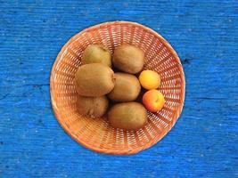 Les kiwis et les abricots dans un panier en osier sur un fond de table en bois photo