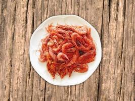 Crevettes sur une plaque blanche sur un fond de table en bois