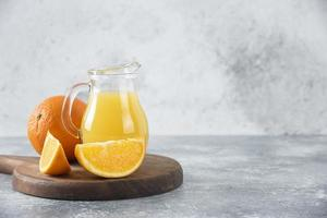 un pichet en verre de jus de fruits frais avec des fruits orange entiers et tranchés placés sur une planche de bois