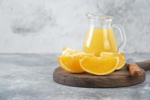 Tranches d'orange avec un pichet en verre de jus de fruits frais placé sur une planche ronde en bois photo