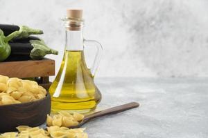 pâtes crues en forme de coquille avec une bouteille en verre d'huile et une boîte en bois pleine de légumes frais photo