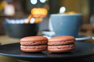 Close up de macarons au chocolat dans une assiette sur la table de café