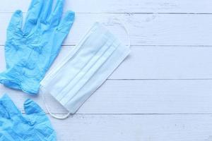 masques chirurgicaux et gants médicaux sur fond de bois photo