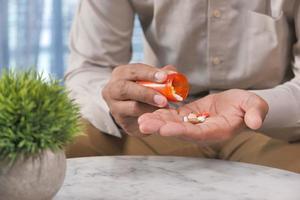 homme prenant des médicaments dans un flacon de pilules