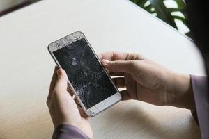 personne tenant un téléphone intelligent cassé