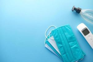 masques chirurgicaux, thermomètre et désinfectant pour les mains sur fond bleu photo