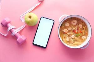 concept de remise en forme avec ruban à mesurer, pomme, téléphone intelligent et cloche stupide sur fond rose photo