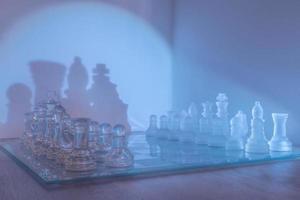 Pièces d'échecs et plateau lumineux en verre dans une brume violette
