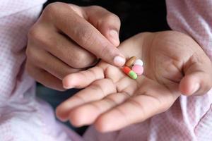personne tenant des pilules colorées