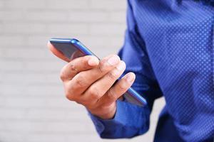 homme tenant un téléphone bleu sur fond neutre photo