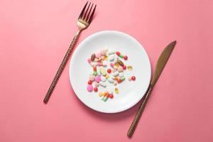 pilules colorées sur une assiette avec fond rose photo