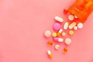 pilules colorées se renversant sur fond rose photo