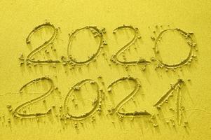 inscription sur le sable d'or 2020 et 2021, tonique dans la couleur tendance de l'année 2021 photo