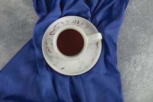 une tasse en céramique blanche sur une nappe bleue photo
