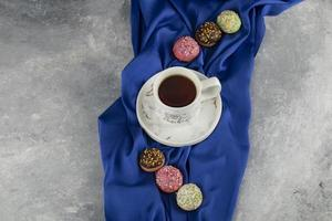 délicieux beignets colorés avec une tasse de thé photo
