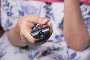 main de femme tenant la télécommande du téléviseur photo