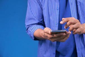 Gros plan de la main du jeune homme à l'aide de téléphone intelligent sur fond bleu photo