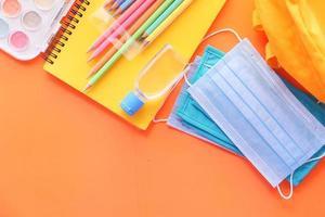 fournitures scolaires colorées sur fond orange photo
