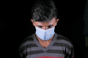 un jeune homme avec un masque de protection isolé sur fond noir photo