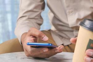 gros plan, de, jeune homme, main, utilisation, téléphone intelligent photo