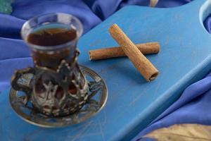 un thé en verre avec des bâtons de cannelle sur une planche à découper en bois photo