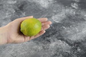 main de femme tenant un citron vert frais photo