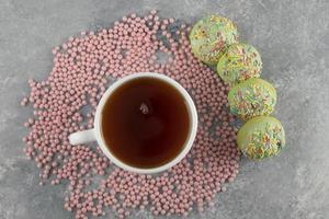 beignets verts sucrés avec une tasse de thé photo