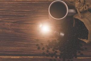 tasse à café et une ampoule émettant de l'énergie sur une table en bois